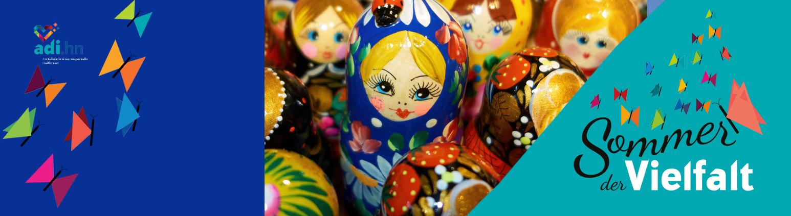Links sind Schmetterlinge und das Logo der adi eingeblendet. In der Mitte sieht 7 russische Puppen in verschiedenen Größen, die eng nebeneinander stehen. In der Mitte ist eine größere Puppe mit blauem Kopftuch und gelben Haaren. Sie schaut aus dem Bild heraus. Die Gruppe ist von schräg oben fotografiert. Rechts ist das Logo vom Sommer der Vielfalt