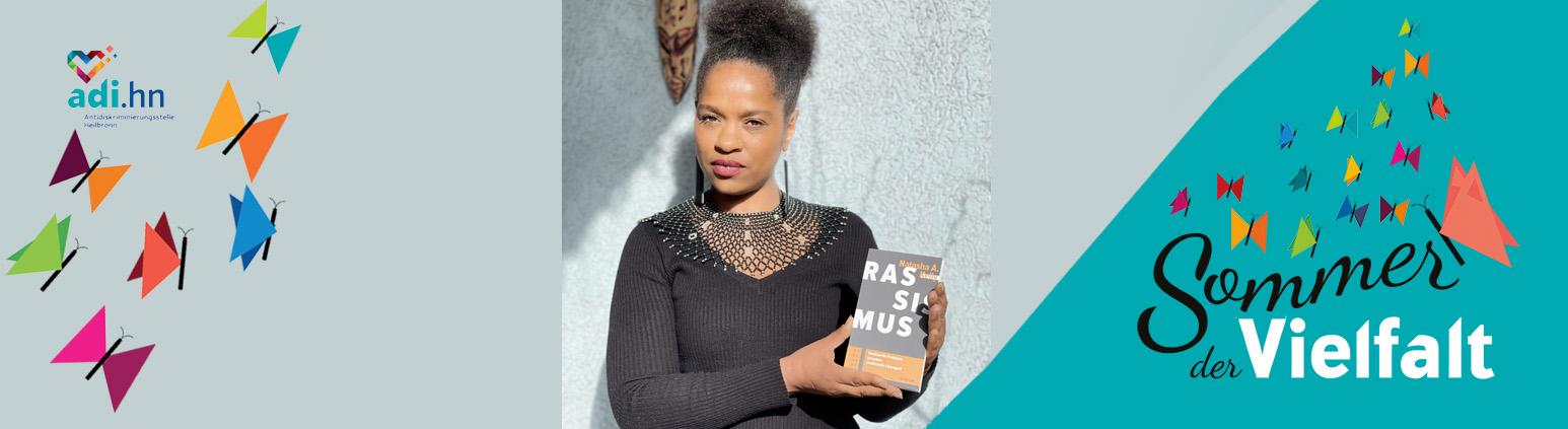 """Links sind Schmetterlinge und das Logo der adi eingeblendet. In der Mitte ist ein Foto von Natasha Kelly. Sie ist eine junge Schwarze Frau. Sie hat ihre Haare zu einem Zopf auf dem Kopf zusammen gebunden und trägt lange Ohrringe. Sie trägt einen braunen Pullover und eine breite Kette im Lochmuster. Sie sieht ernst aus. Sie hält ihr Buch """"Rassismus"""" in der Hand. Rechts ist das Logo vom Sommer der Vielfalt"""